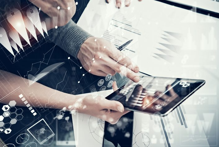 Photo female hands holding modern tablet and man touching screen.Businessmans crew working new investment project office.Using electronic devices.Graphics icons, stock exchanges interface.