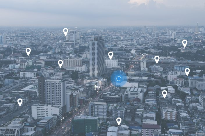 Searching location on map and pin above blue tone city scape and network connection, internet of things, satellite navigation system concept